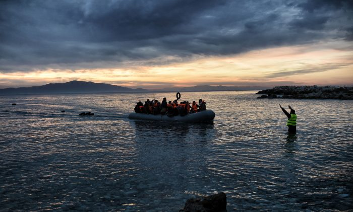 Refugees and migrants massed onto an inflatable boat reach Mytilene, northern island of Lesbos, after crossing the Aegean sea from Turkey on Febr. 17, 2016. (Aris Messinis/AFP/Getty Images)