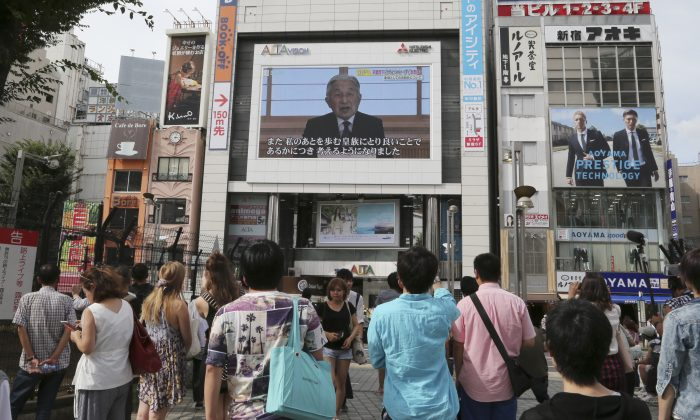 People watch a screen showing Japanese Emperor Akihito delivering a speech in Tokyo, Monday, Aug. 8, 2016. The Japanese emperor, in a rare address to the public, signaled Monday his apparent wish to abdicate by expressing concern about his ability to carry out his duties fully. (AP Photo/Koji Sasahara)