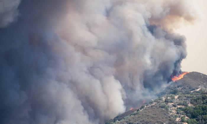 A wildfire burns over a ridge towards Summit Valley, Calif. on Aug. 7. (James Quigg/The Daily Press via AP)