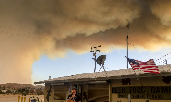 Trevor Rainwater watches a wildfire burn into Summit Valley from the Joshua Inn which was evacuated moments later in Hesperia Calif. on Aug. 7. (James Quigg/The Daily Press via AP)