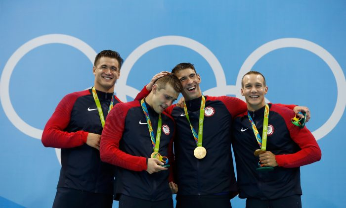 RIO DE JANEIRO, BRAZIL - AUGUST 07:  Gold medalists Nathan Adrian, Ryan Held, Michael Phelps and Caeleb Dressell of the United States pose on the podium during the medal ceremony for the Final of the Men's 4 x 100m Freestyle Relay on Day 2 of the Rio 2016 Olympic Games at the Olympic Aquatics Stadium on August 7, 2016 in Rio de Janeiro, Brazil.  (Photo by Clive Rose/Getty Images)