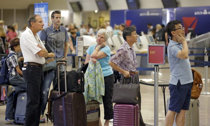 Delta passengers stand in line as the carrier slogged through day two of its recovery from a global computer outage in Salt Lake City on Aug. 9, 2016. (AP Photo/Rick Bowmer)