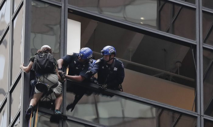 New York Police officers attach a climbing rope and carabiner to a man who was attempting to scale Trump Tower in New York on Aug. 10, 2016. (AP Photo/Julie Jacobson)