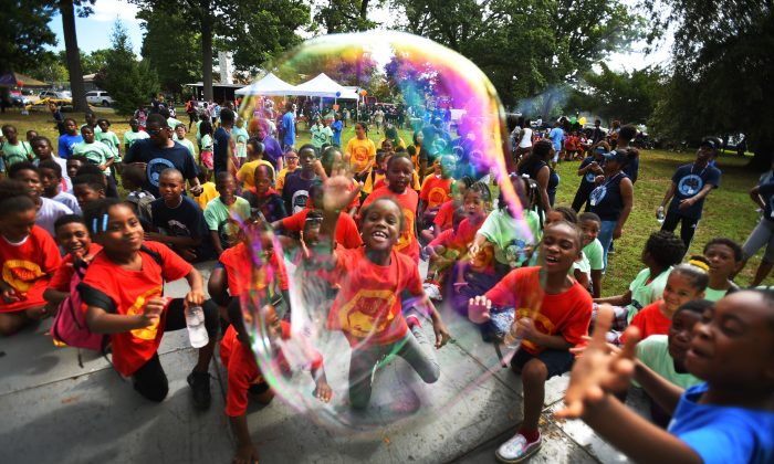 """Children try to grab a giant soap bubble during the annual """"Day in the Sun"""" end of summer camp at Eastside Park in Paterson, N.J., on Aug. 11, 2016. (Mitsu Yasukawa/The Record of Bergen County via AP)"""