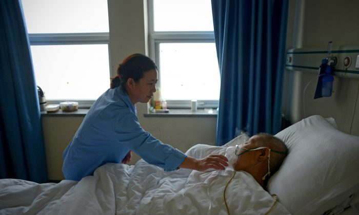 A man suffering from pneumonia receives treatment in a ward at a hospital in Beijing on Dec. 9, 2015. (WANG ZHAO/AFP/Getty Images)