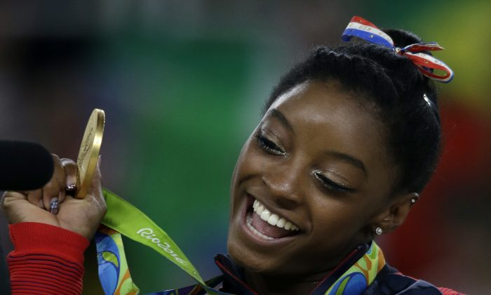 Simone Biles displays her gold medal for floor during the artistic gymnastics women's apparatus final at the 2016 Summer Olympics. (AP Photo/Rebecca Blackwell)