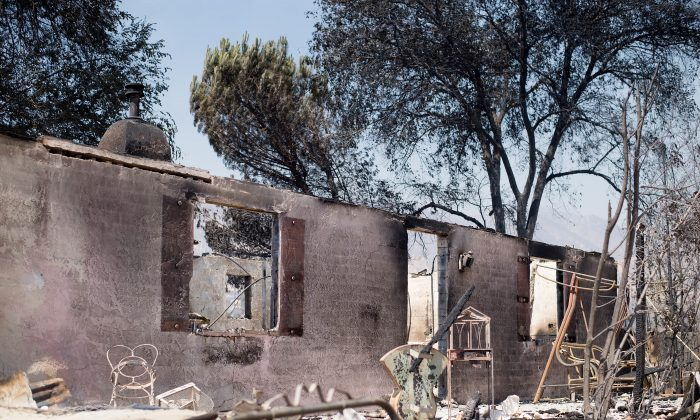 A burned out residence stands amid rubble on Highway 138 after the Blue Cut Fire burned through Phelan, Calif., on Aug. 18. (AP Photo/Noah Berger)