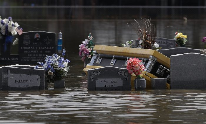 A casket is seen in a flooded cemetery on August 17, 2016 in Sorrento, Louisiana. Tremendous downpours has resulted in disastrous flooding, responsible for at least seven deaths and thousands of homes being damaged. (Photo by Joe Raedle/Getty Images)