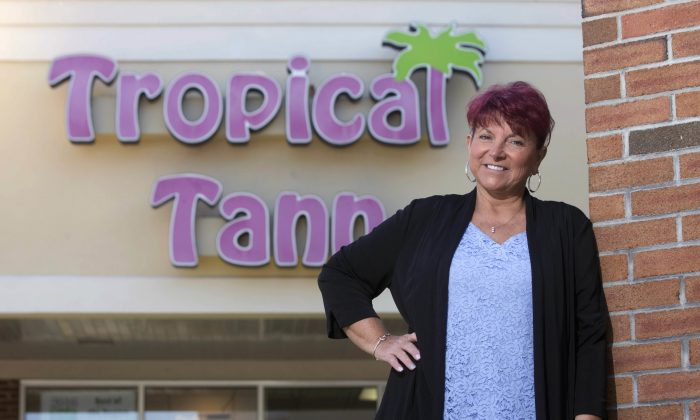 Kim Arnold stands for a photo outside her Tropical Tann business in Queensbury, N.Y., on June 17, 2016. Arnold said she and her husband had to close their third location in 2015 because of a 10 percent tax on tanning in the Affordable Care Act. (AP Photo/Mike Groll)