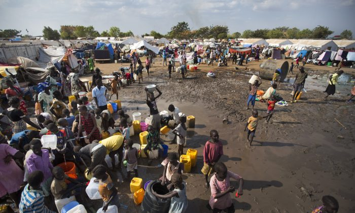 Displaced people gather around a water truck to fill containers at a United Nations compound which has become home to thousands of people displaced by the recent fighting, in the capital Juba, South Sudan, on Dec. 29 2013. (AP Photo/Ben Curtis)