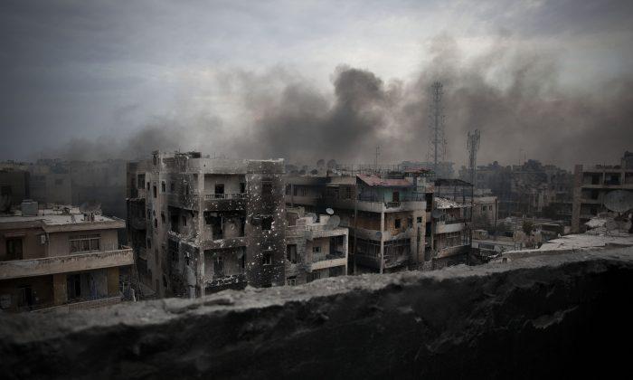 Smoke rises over Saif al-Dawla District in Aleppo, Syria, Oct. 2, 2012. (AP Photo/ Manu Brabo)