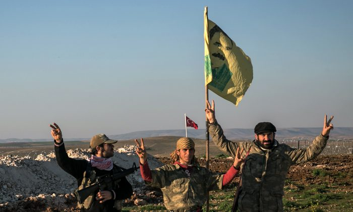 In this Feb. 22, 2015 file photo, Syrian Kurdish militia members of the YPG make a V-sign next to a drawing of Abdullah Ocalan, jailed Kurdish rebel leader, in Esme village in Aleppo province, Syria.  (Mursel Coban/Depo Photos via AP, File)