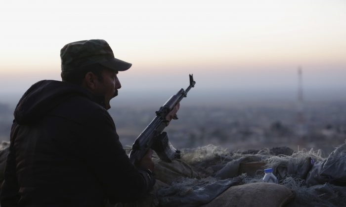 A Kurdish fighter, known as a peshmerga, yawns as he stands guard on the frontline in Sinjar, Iraq, on Nov. 13, 2015. (AP Photo/Bram Janssen)