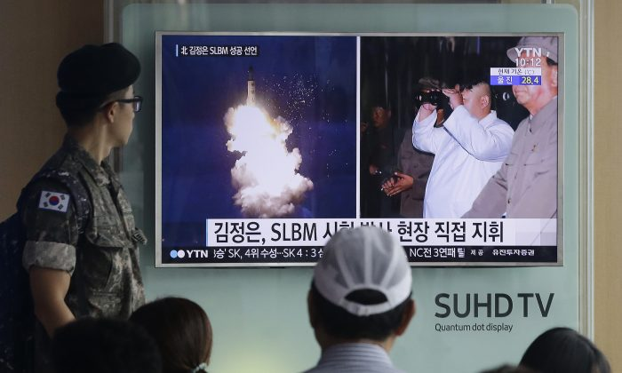 A South Korean Army soldier watches a TV news program showing images published in North Korea's Rodong Sinmun newspaper of North Korea's ballistic missile believed to have been launched from underwater and North Korean leader Kim Jong-un, at Seoul Railway station in Seoul, South Korea, on Aug. 25, 2016. (AP Photo/Ahn Young-joon)
