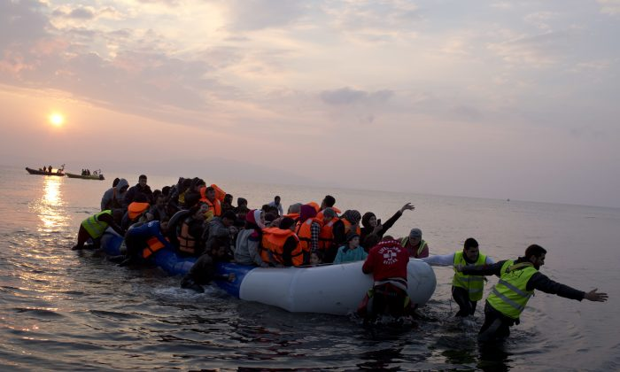 Volunteers help migrants and refugees on a dingy as they arrive at the shore of the northeastern Greek island of Lesbos, after crossing the Aegean sea from Turkey on March 20, 2016. (AP Photo/Petros Giannakouris)