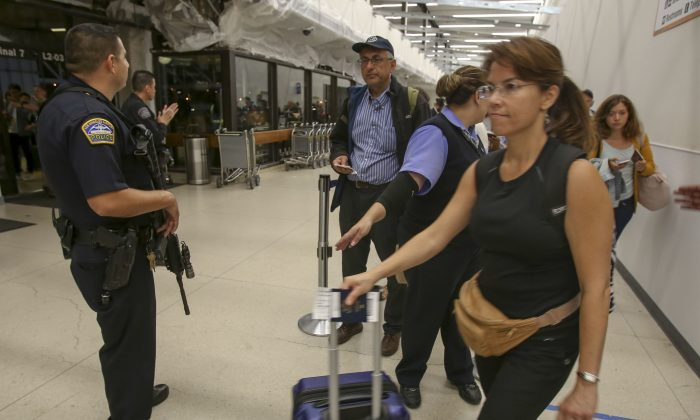 A police officer stands guard as passengers wait in line at Terminal 7 in Los Angeles International Airport Aug. 28, 2016. (AP Photo/Ringo H.W. Chiu)