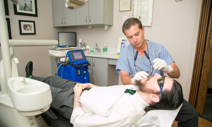 Dr. Chris Chondrogiannis with a patient at Madison Avenue Periodontics in Manhattan, N.Y. (Samira Bouaou/Epoch Times)