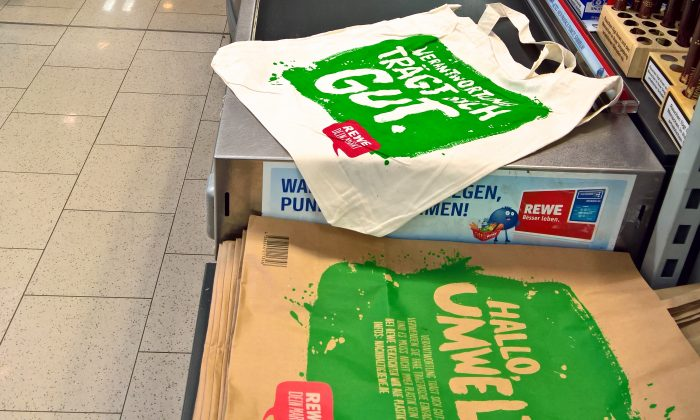 "Cotton and paper shopping bags in REWE supermarket in Germany.   The bags read ""Hello Environment"" in German. (Ilya Rzhevskiy/Epoch Times)"