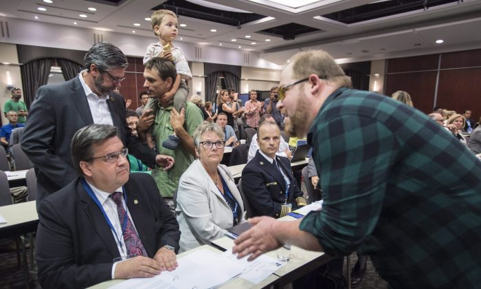 A demonstrator confronts Montreal mayor Denis Coderre during the National Energy Board public hearing into the proposed $15.7-billion Energy East pipeline project in Montreal on Aug. 29. (The Canadian Press/Paul Chiasson)