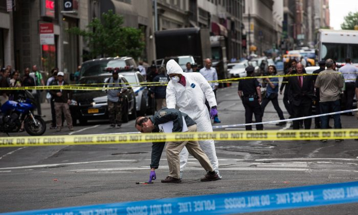 Crime scene investigators inspect a hammer used in an attack on a police officer in New York City on May 13, 2015.  (Andrew Burton/Getty Images)