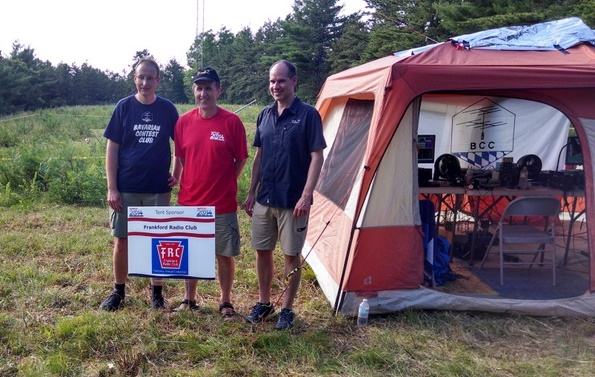 The German team and their Polish referee of the the 2014 World Radiosport Team Championship standing beside their tent at their site in the  Myles Standish State Forest. (L–R) Manfred Wolf, referee Wes Kosinski, and Stefan von Baltz. (Courtesy of J. K. George)
