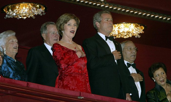 Former US President George H.W. Bush (L2) and his wife Barbara (L) sing the US National Anthem with their son US President George W. Bush (C) and wife Laura, with US Secretary of State Colin Powel (R) and wife Alma  (PAUL J.RICHARDS/AFP/Getty Images)