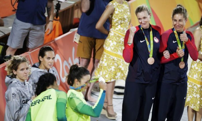 Bronze medalists from the United States, April Ross, from right, and Kerri Walsh Jennings, give a thumbs-up as Brazil's Agatha Bednarczuk, bottom left, and Barbara Seixas are awarded the silver medal after losing in the women's beach volleyball gold medal match to Germany's Laura Ludwig, left, and Kira Walkenhorst at the 2016 Summer Olympics in Rio de Janeiro, Brazil, Wednesday, Aug. 17, 2016. (AP Photo/David Goldman)