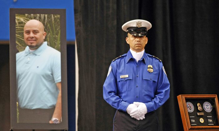 FILE - In this Nov. 12, 2013 file photo, a Transportation Security Administration officer stands in front of a portrait of slain TSA officer Gerardo Hernandez during his public memorial at the Los Angeles Sports Arena. Paul Ciancia, the gunman who killed Hernandez and wounded three others during a shooting rampage at Los Angeles International Airport three years ago, has agreed to plead guilty. Ciancia, 26, faces a mandatory life sentence for murder and other penalties, according to the plea agreement filed Thursday, Sept. 1, 2016, in U.S. District Court that calls for him to plead guilty to all charges. (Al Seib/Los Angeles Times via AP, Pool, File)