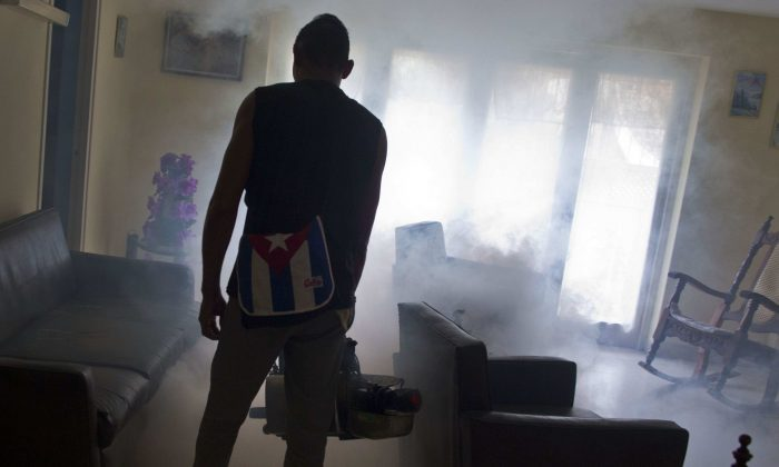 In this Aug. 26, 2016 photo, a government fumigator sprays a home for mosquitos in Havana, Cuba. (AP Photo/Ramon Espinosa)