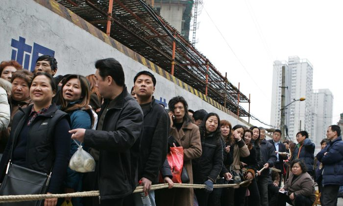 Chinese people form lines outside of a construction site waiting to buy quality apartments in Shanghai, China, on March 2, 2005. (China Photos/Getty Images)