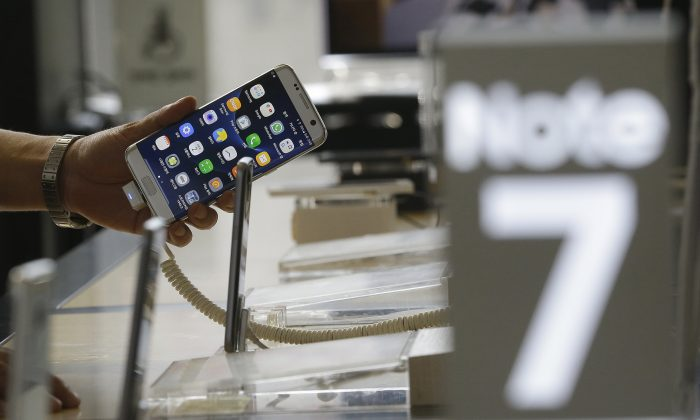 A customer holds a Samsung Electronics Galaxy Note 7 smartphone at the headquarters of South Korean mobile carrier KT in Seoul, South Korea, on Sept. 2, 2016. (AP Photo/ahn Young-joon)
