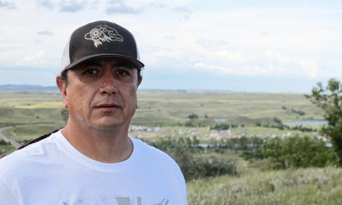 Standing Rock Sioux Chairman Dave Archambault II poses for a photo on Aug. 26, 2016, near Cannon Ball, N.D., on the Standing Rock Sioux Reservation overlooking an encampment where Native Americans from across North America have gathered to join his tribe's growing protest against a $3.8 billion four-state oil pipeline. About 30 people, including Archambault himself, have been arrested in recent weeks for interfering with construction of the Dakota Access pipeline. (AP Photo/James MacPherson)