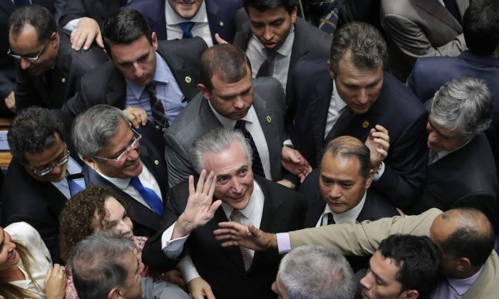 Brazil's President Michel Temer (C) is surrounded by senators as he arrives to take the presidential oath at the National Congress, in Brasilia, Brazil, on Aug. 31, 2016. (AP Photo/Eraldo Peres)
