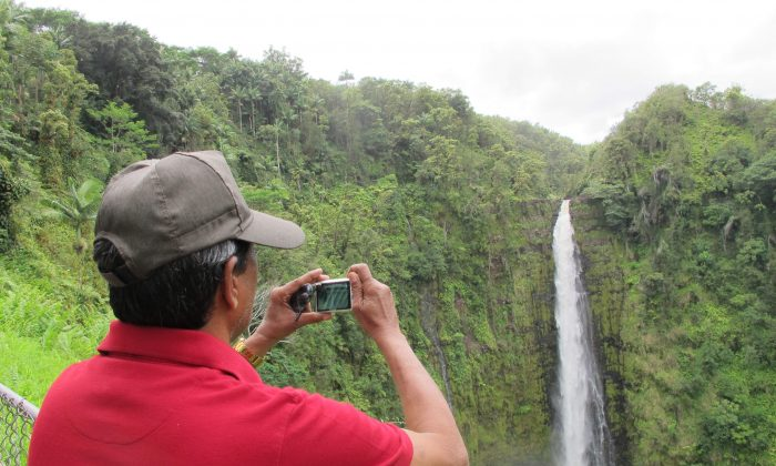 A man takes a photo of Akaka Falls in Honomu, Hawaii, on Sept. 2, 2016. (AP Photo/Audrey McAvoy)