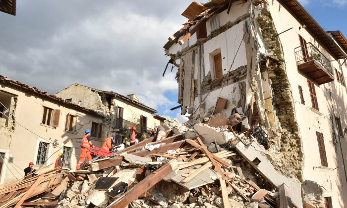 Rescuers clear debris while searching for victims in damaged buildings in Arquata del Tronto, Italy, on Aug. 24, 2016. (Giuseppe Bellini/Getty Images)