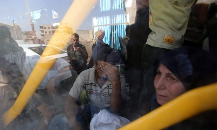 People are seen inside a bus, as they are being evacuated from the town of Daraya outside the capital Damascus on Aug. 26, 2016, under a deal agreed between the government and opposition fighters after a four-year army siege. (Youssef Karwashan/AFP/Getty Images)