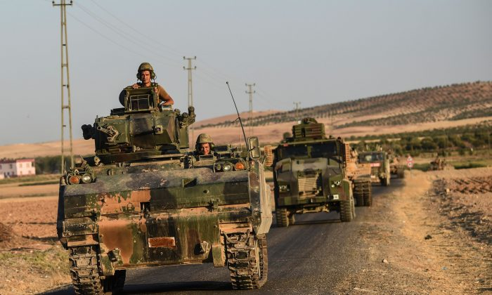 Turkish soldiers stand in a Turkish Army tank driving back to Turkey from the Syrian-Turkish border town of Jarabulus, in the Turkish-Syrian border town of Karkamis, on Sept. 2, 2016. (Bulent Kilic/AFP/Getty Images)