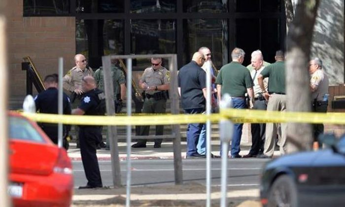 Law enforcement officials and others are seen outside the lobby of the Fresno County Jail after reports of an active shooter in the main lobby of the jail in downtown Fresno, Calif., Saturday, Sept. 3, 2016. Two unarmed officers were critically injured after being shot by a visitor in the lobby of the central California jail, authorities said Saturday. Authorities said officers from the secured areas inside the jail ran to the lobby, where a lieutenant fired shots at the gunman, identified as 37-year-old Thong Vang, who was taken into custody. (Silvia Flores/The Fresno Bee via AP)