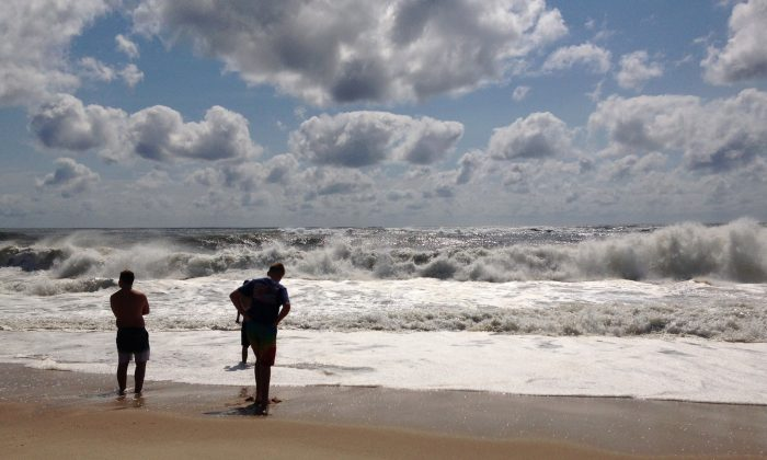 Beachgoers stand at the edge of the water, Sunday, Sept. 4, 2016, in Bridgehampton, N.Y., on the southeastern shore of Long Island, where the effects of storm system Hermine could be seen in the rough surf and a ban on swimming. Hermine spun away from the U.S. East Coast on Sunday, removing the threat of heavy rain but maintaining enough power to churn dangerous waves and currents and keep beaches off-limits to disappointed swimmers and surfers during the holiday weekend. (AP Photo/Jennifer Peltz)