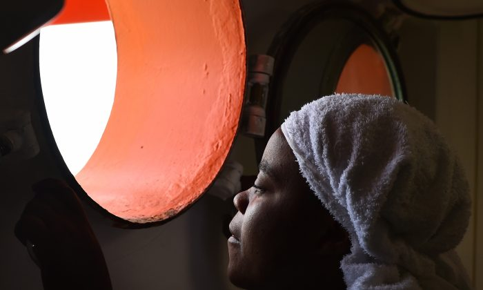 """A woman looks through a window of rescue ship """"Aquarius"""" as more the 380 migrants arrive in the port of Cagliari, Sardinia, on May 26, 2016, two days after being rescued near the Libyan coasts. The Aquarius is a former North Atlantic fisheries protection ship now used by humanitarians SOS Mediterranee and Medecins Sans Frontieres (Doctors Without Borders) which patrols to rescue migrants and refugees trying to reach Europe crossing the Mediterranean sea aboard rubber boats or old fishing boat. (Gabriel Bouys/AFP/Getty Images)"""
