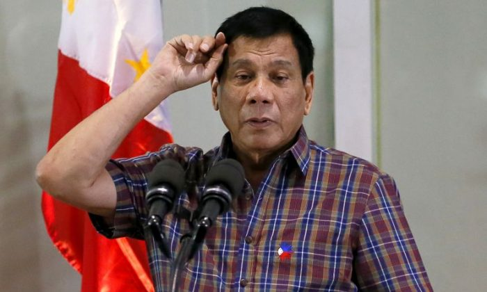 FILE - In this Aug. 31, 2016, file photo, Philippine President Rodrigo Duterte gestures as he addresses Overseas Filipino Workers who were repatriated back to the country at the Ninoy Aquino International Airport in Pasay city, south of Manila, Philippines. Duterte, who disparaged the pope and others who controvert his worldview, warns U.S. President Barack Obama on Monday, Sept. 5, 2016, not to question him about extrajudicial killings. (AP Photo/Bullit Marquez, File)