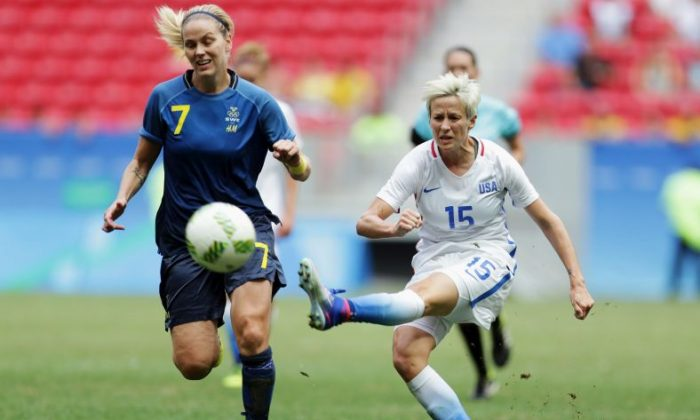 In this Friday, Aug. 12, 2016, file photo, United States' Megan Rapinoe, right, kicks the ball past Sweden's Lisa Dahlkvist. (AP Photo/Eraldo Peres, File)