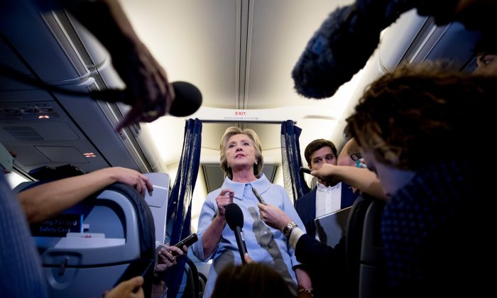 Democratic presidential candidate Hillary Clinton speaks to members of the media on her campaign plane while traveling to Quad Cities International Airport in Moline, Ill., Monday, Sept. 5, 2016. (AP Photo/Andrew Harnik)