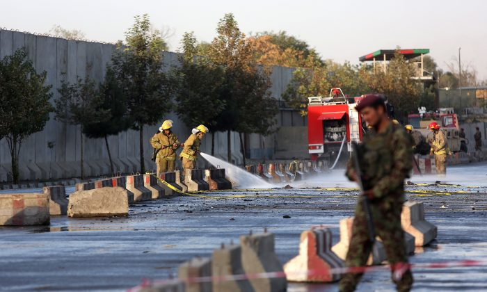 An Afghan soldier inspects the site of suicide attack In Kabul near Afghanistan's Defense Ministry, Monday, Sept. 5, 2016.  Twin bombings near the Afghan Defense Ministry have killed dozens of people in an attack claimed by the Taliban. (AP Photo/Rahmat Gul)