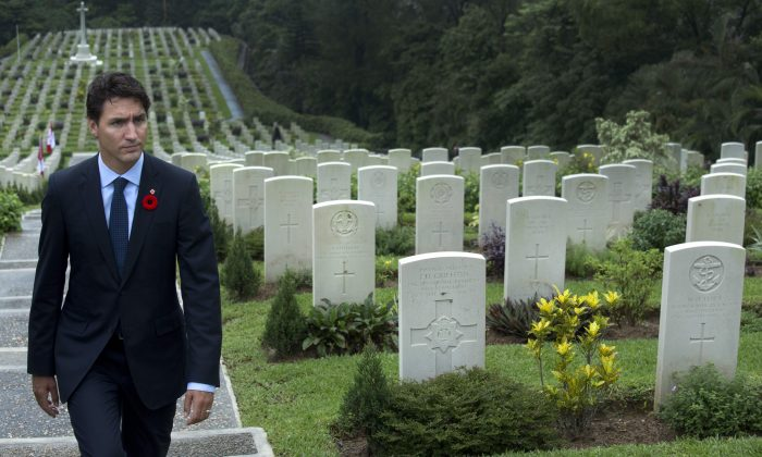 Prime Minister Justin Trudeau walks amongst the headstones at the Sai Wan war cemetery in Hong Kong on Sept. 6, 2016. The Sai Wan Bay Memorial includes the names of 228 Canadians who died in the defense of Hong Kong during the World War II. (AP Photo/Vincent Yu)