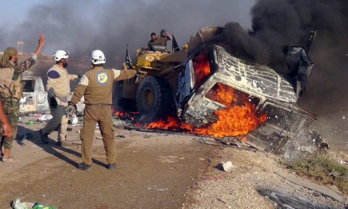 This photo provided by the Syria Press Center (SPC), an anti-government media group, shows rescue workers using a bulldozer to remove a burned van after airstrikes hit west of the town of Suran in Hama province, Syria, Thursday Sept. 1, 2016, killing a dozen people. Suspected government warplanes carried out a series of airstrikes in Hama amid a lightning advance by insurgents on government-controlled areas in the province. (Syria Press Center via AP)
