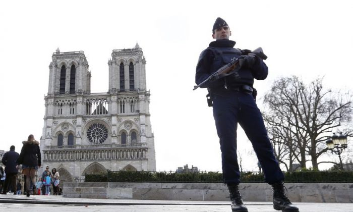 In this March 27, 2016 file photo, a French Police officer stands guards as worshipers arrive for the Easter mass at Notre Dame Cathedral, in Paris.  (AP Photo/Francois Mori, File)
