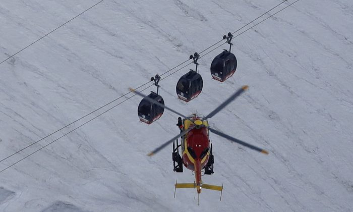 An EC-135 helicopter operated by the French Societe' Civile hovers, Friday, Sept. 9, 2016, near three cars of the Panoramic Mont Blanc cable car that stalled around 4 p.m. (1400 GMT) on Thursday, after its cables reportedly tangled. The cable car carrying tourists stopped working at high altitude over the Mont Blanc massif in the Alps on Thursday, prompting a major rescue operation and leaving 45 people trapped in midair overnight, France's interior minister said. (AP Photo/Luca Bruno)