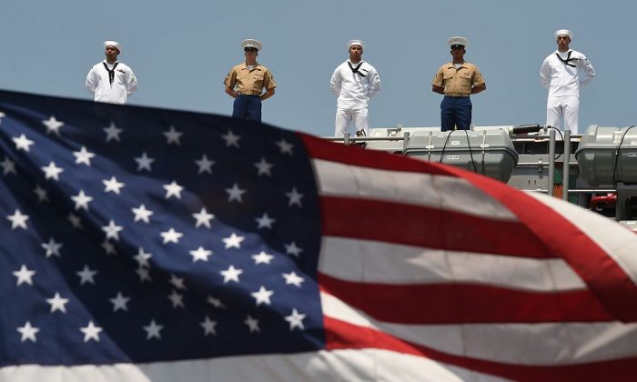 The US Flag blows in the wind as Sailors and Marines stand on the deck of the USS Bataan (LHD 5) as it arrives into Pier 88  during the 'Parade of Ships'  ceremony to kick off  Fleet Week in New York on May 25, 2016.   Thousands of sailors, marines and Coast Guardsmen from the US Navy and US Coast Guard as well as from international navy ships attend the celebrations. / AFP / TIMOTHY A. CLARY        (Photo credit should read TIMOTHY A. CLARY/AFP/Getty Images)