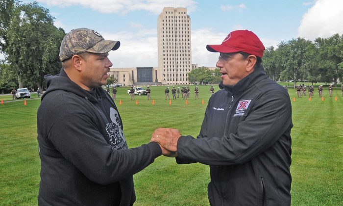 Standing Rock Sioux tribal chairman Dave Archambault II (R) greets Wayland Gray, of Muskogee Creek Hickory Ground, Okla., at the organized protest on the North Dakota state capitol grounds in Bismarck, N.D., on Sept. 9, 2016. (Tom Stromme/The Bismarck Tribune via AP)